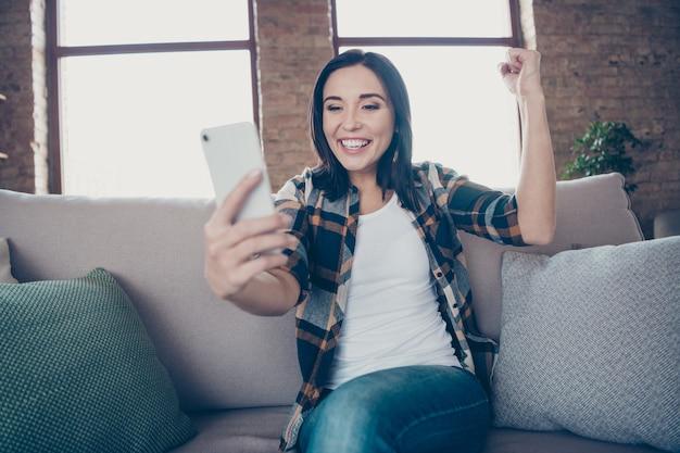Фотография симпатичной дамы с телефоном, читающей лучшие новости о стартап-проекте, поднимающая кулак, сидя на уютном диване в повседневной одежде, квартира в помещении