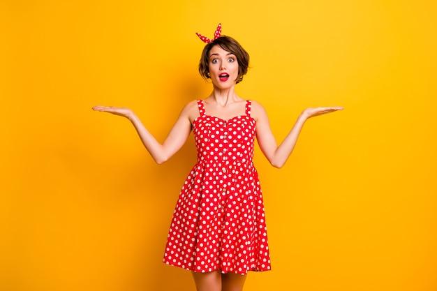 Фотография симпатичной модели-менеджера с распростертыми объятиями продукт, представляющий классную новинку, два варианта одежды в стиле ретро, летнее красное белое платье в горошек, оголовье, изолированная стена желтого цвета
