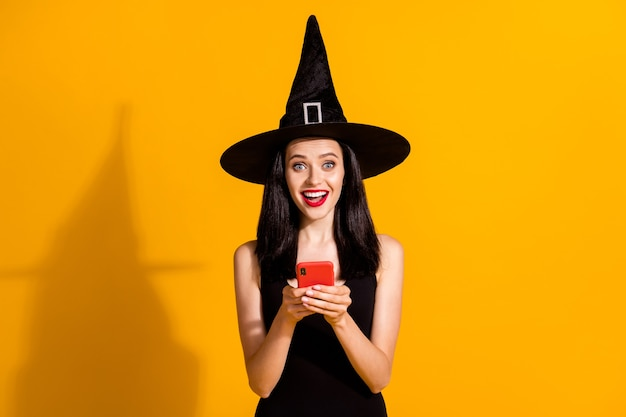 かなり素敵な若いマジシャンの女性が電話を持って興奮している写真を読んで休日の投稿を共有する友人が好きな黒の魔法使いの帽子のドレスを分離した明るい黄色の背景