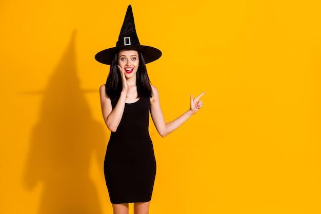 かなり素敵な若い魔術師の女性の直接指の空のスペースの写真は、メイジのための最速のほうきを提案します手顔着用黒の帽子ドレス孤立した明るい黄色の背景