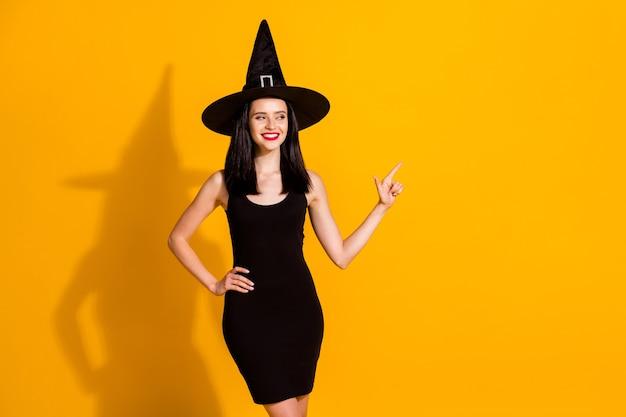 かなり素敵な若い魔術師の女性の写真直接指の外観空のスペースは手作りの魔法のアイテムを提供します割引着用黒の帽子ドレス孤立した明るい黄色の色の背景