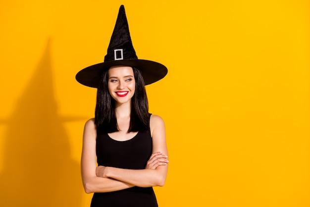 かなり素敵な若い魔術師の女性の写真は手を組んで自信を持って見える空のスペースずるい笑顔準備トリックを着用する黒い帽子のドレス孤立した明るい黄色の背景