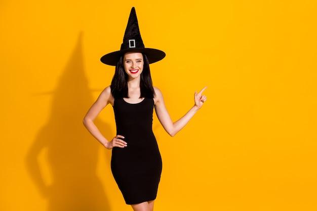 かなり素敵な若い魔術師の魔術師の女性の写真は、直接指の空きスペースを笑顔で輝いていますポーションの販売をお勧めします黒の帽子のドレスを着用して明るい黄色の背景を分離しました