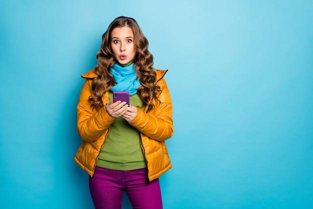 Фото симпатичной миллениальной дамы держите телефон за руки читать распродажу торговую рекламу носить желтый пальто шарф фиолетовые брюки зеленый джемпер изолированный синий цвет стены