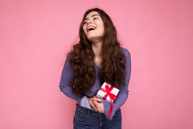분홍색 배경 위에 절연 꽤 긍정적 인 웃는 갈색 곱슬 젊은 여자의 사진