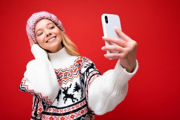 따뜻한 니트 모자와 겨울 따뜻한 스웨터를 입고 꽤 긍정적인 젊은 금발 여자의 사진