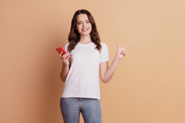 Фотография симпатичной женщины-промоутера, держащей телефон, указывает на пустое пространство указательным пальцем, позирующую на бежевом фоне