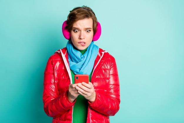 かなり怖い女性の写真は電話を持って悪い否定的なブログのコメントを読んで唇を噛むカジュアルな赤いコートスカーフピンクのイヤーウォーマーセーター孤立したティールカラーの壁