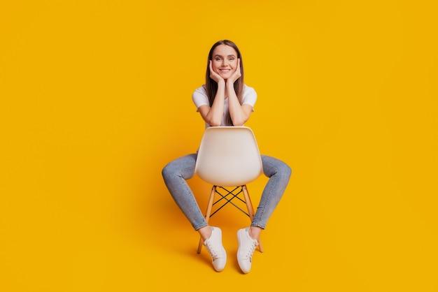 かなり光沢のある女性の写真座っている椅子の手頬骨は黄色の背景にポーズをとって白いtシャツを着ています