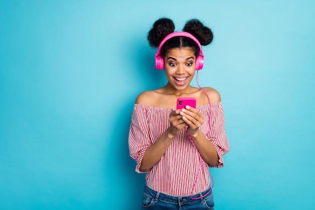 꽤 충격을당한 어두운 피부 아가씨의 사진 전화는 좋은 소식을 읽고 음악을 듣고 현대 기술 이어폰 착용 빨간색 흰색 줄무늬 셔츠 벗은 어깨 절연 파란색 벽