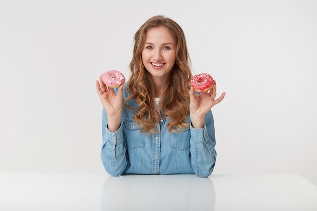Фотография довольно улыбающейся молодой женщины с длинными светлыми волнистыми волосами, держит в руках пончики, одетая в джинсовую рубашку. смотрит в камеру, изолированные на белом фоне.