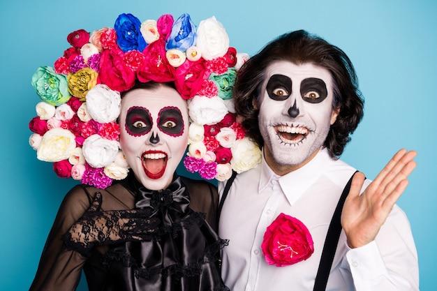 Фото довольно жуткой пары мужчина леди девушка обнимаются сюрприз скидка религиозный фестиваль ритуальные предметы носить черное платье костюм смерти розы повязка на подтяжках изолированный синий цвет фона