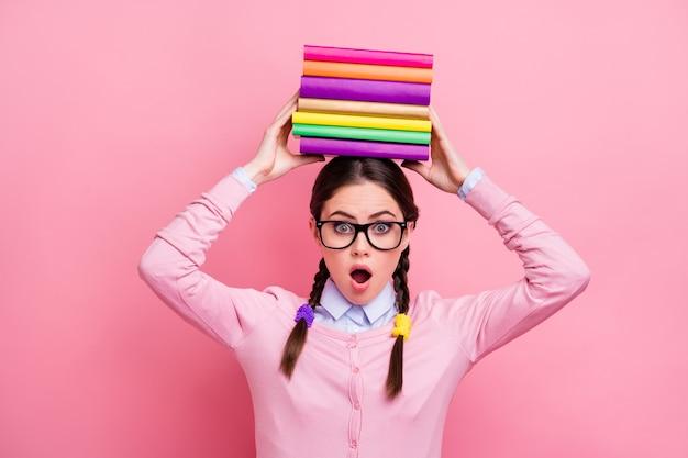 かわいい学生の女性の写真は、試験を準備している頭に文学の山を保持します大学大学の大きな宿題は、シャツのプルオーバーの仕様を分離したピンク色の背景を圧倒しました