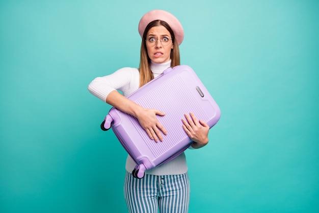 Фото довольно напуганной женщины-путешественницы обнять большой фиолетовый чемодан регистрации в аэропорту бояться летать носить спецификации розовый берет белая водолазка полосатые джинсы изолированный бирюзовый цвет фона