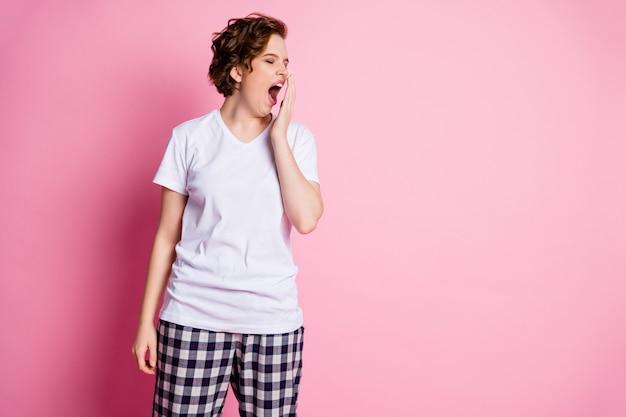 꽤 피곤한 여자의 사진은 분홍색 벽에 졸린 열린 하품 입 근처에 손을 잡습니다.