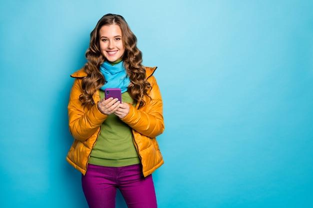 きれいな旅行者の女性の写真は電話検索オンラインマップを保持します最高の旅行方法情報は黄色のオーバーコートスカーフバイオレットのズボンを着用します