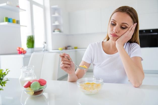 スプーンを持っているかなり動揺している主婦の写真は、屋内で退屈な座っているテーブルの白い光のキッチンをダイエットするのにうんざりしている牛乳の朝食のコーンフレークを食べたくない