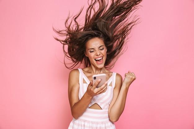 ピンクの壁に隔離された、笑顔で髪を振ってスマートフォンを保持しているドレスを着ているきれいな女性20代の写真