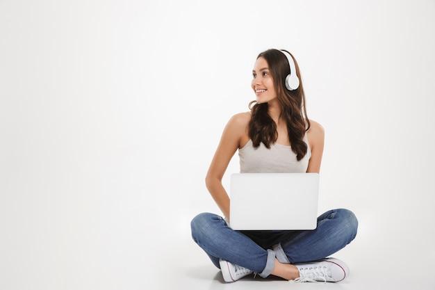 Фотография симпатичной женщины, слушающей музыку или болтающей, используя наушники и ноутбук, сидя со скрещенными ногами на полу, над белой стеной