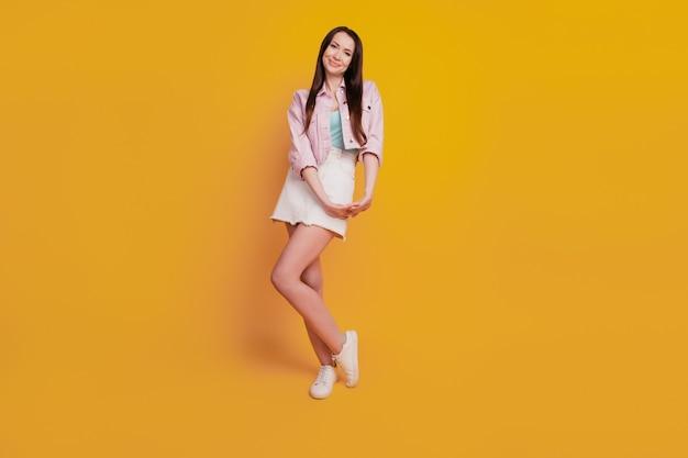 Фото красивой молодой женщины, позирующей изолированной на желтом фоне.