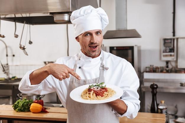 Фотография профессионального мужчины-вождя в белой форме, держащего тарелку с макаронами