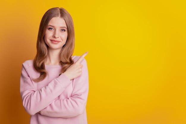 プロモーターの女の子の指の直接の空きスペースの写真は黄色の背景に宣伝します