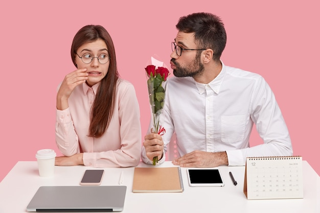 困惑した魅力的な女性の写真は歯を食いしばって、バラの花束を与えるハンサムな男を恥ずかしがり屋の表情で見ます