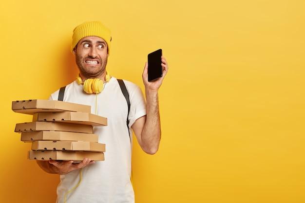 困惑した配達人の写真は、ピザの箱を運び、現代のスマートフォンを持ち、一度に多くの電話や注文を受け、カジュアルな服を着て、黄色い壁に立ちます