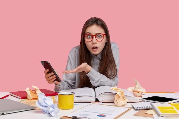 На фото озадаченная эмоциональная дама в очках, держит современный сотовый телефон, чувствует замешательство, читает научную литературу, ошеломленная, чтобы получить уведомление.