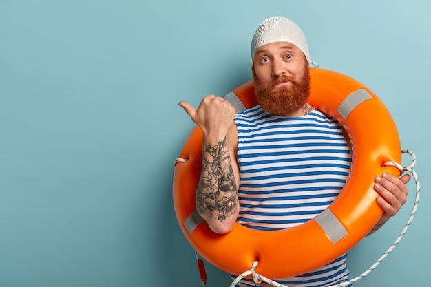 의아해하는 남성 수영 선수 또는 강사의 사진이 엄지 손가락을 왼쪽으로 가리키며 복사 공간에 관심을 기울입니다.