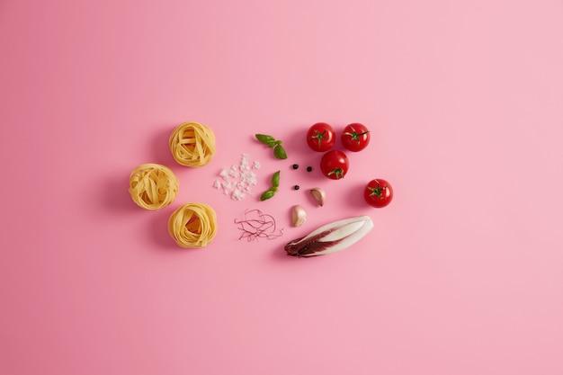 調理する材料が入った生パスタの巣の写真。バラ色の背景に赤いサラダチコリ、チェリートマト、バジル、ニンニク、乾燥唐辛子の糸。美味しいマカロニを用意しています。イタリア料理