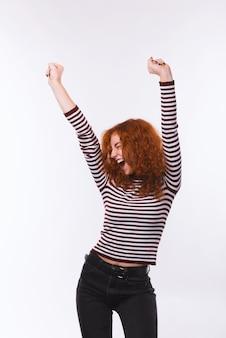 Фотография рыжеволосой женщины, празднующей и танцующей на изолированном фоне