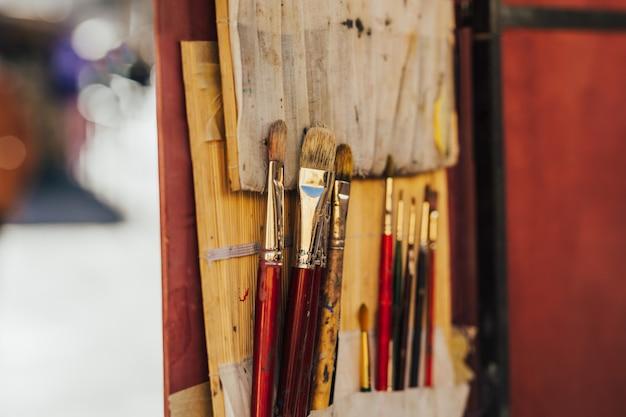 木製の背景に赤いペイントブラシの写真。