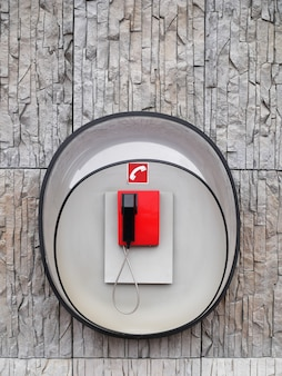 Фотография красного телефона на стене современного здания