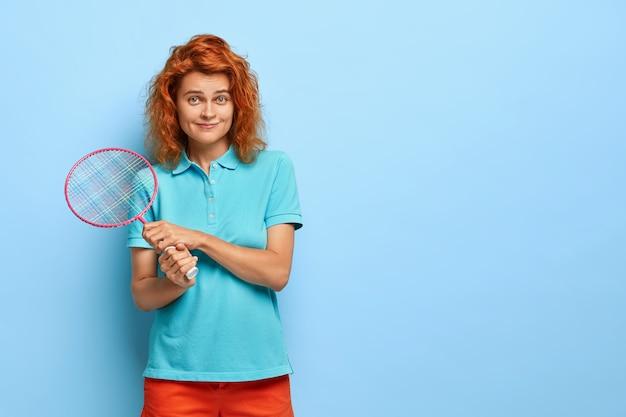 赤髪のティーンエイジャーの写真はバドミントンラケットで立って、カジュアルな服を着て、パートナーがスポーツゲームをプレイするのを待っています