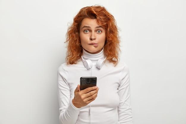 빨간 머리 여성의 사진은 입술을 물고, 놀랍게도 카메라에 보인다.
