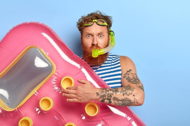 На фото рыжий рыжий мужчина в очках для плавания, маске для подводного плавания, собирается нырять и плавать в море, держит розовый надутый матрас, выглядит серьезно
