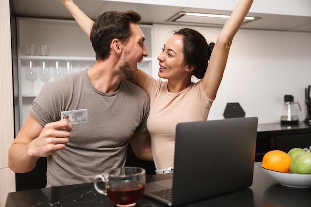 Фотография радующейся пары мужчины и женщины, использующей ноутбук с кредитной картой, сидя на кухне