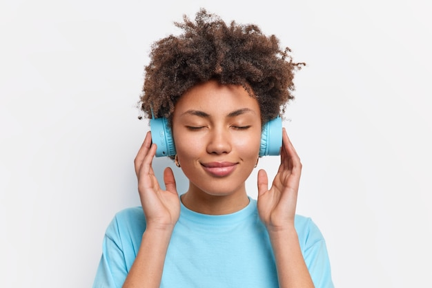 リラックスした縮れ毛の女性の写真は目を閉じて音楽を楽しんでいます白い壁に隔離されたカジュアルな青いtシャツに身を包んだ高音質のヘッドフォンを手にしています。ライフスタイルのコンセプト