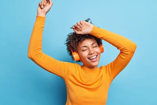 Фотография расслабленной кудрявой молодой женщины, которая держит глаза закрытыми, танцует и ловит каждую частичку музыки, широко улыбается, носит повседневный оранжевый джемпер, использует беспроводные наушники, изолированные на синей стене