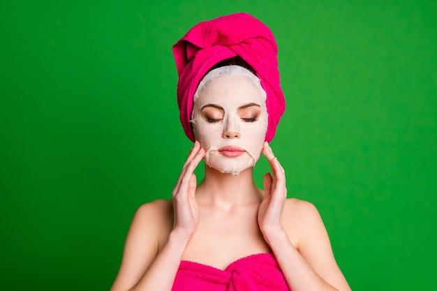 Фото расслабленной дамы нанесите коллагеновую маску на лицо, глаза закрыты, прикоснитесь к щекам, полотенца, тело, голова, изолированный зеленый цвет фона