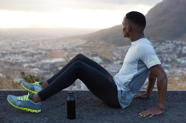 短い髪、黒い肌、冷たい水のボトルを持って高速道路に座って、トラックスーツを着て、脇に集中し、暇な時間を楽しんで、山の景色を楽しみ、トレーニング後に休むリラックスした男の写真。フィットネス、運動