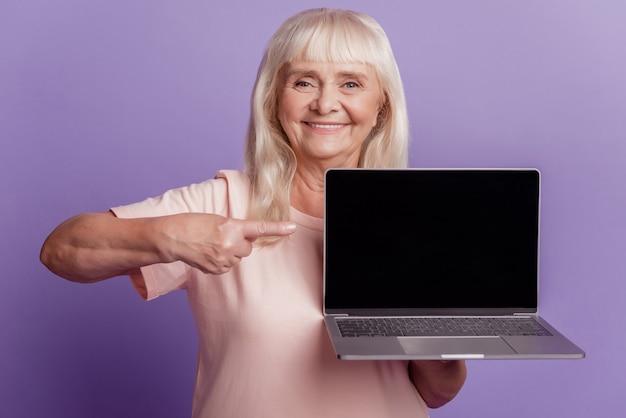 은퇴한 할머니 홀드 노트북 쇼 포인트 손가락 디스플레이 격리된 보라색 배경 사진