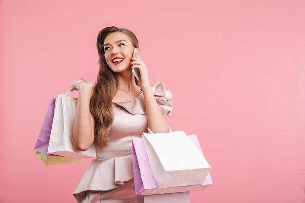 핑크 벽 위에 절연 쇼핑백을 들고 스마트 폰에 얘기하고 드레스에 풍부한 패션 여자 20 대의 사진