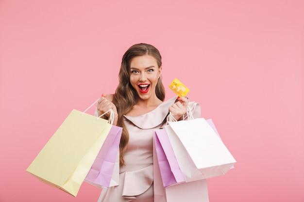 핑크 벽 위에 절연 손에 다른 쇼핑 가방과 신용 카드를 들고 웃 고 드레스에 풍부한 패션 여자 20 대의 사진