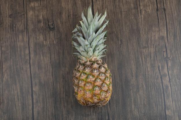 木製の背景に置かれた熟したジューシーなパイナップルの写真