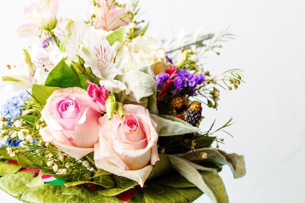 ピンクのバラ、ユリ、空白の白い表面に緑の葉のロマンチックな花束の写真
