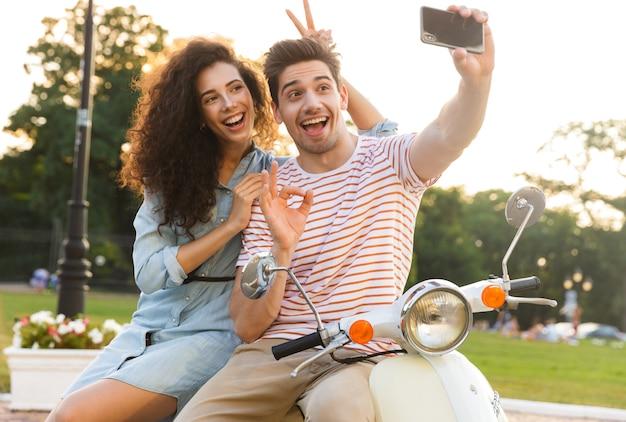 도시 공원에서 스쿠터에 함께 앉아있는 동안 휴대 전화에 셀카를 복용 로맨틱 커플의 사진