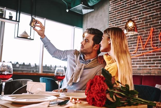 비싼 레스토랑에서 낭만적인 저녁 식사의 사진입니다. 저녁 식사를 하면서 웃고 있는 젊은 부부가 전화로 셀카 사진을 찍고 있다