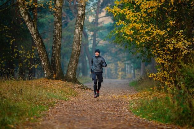 秋の公園で走っているアスリートの写真
